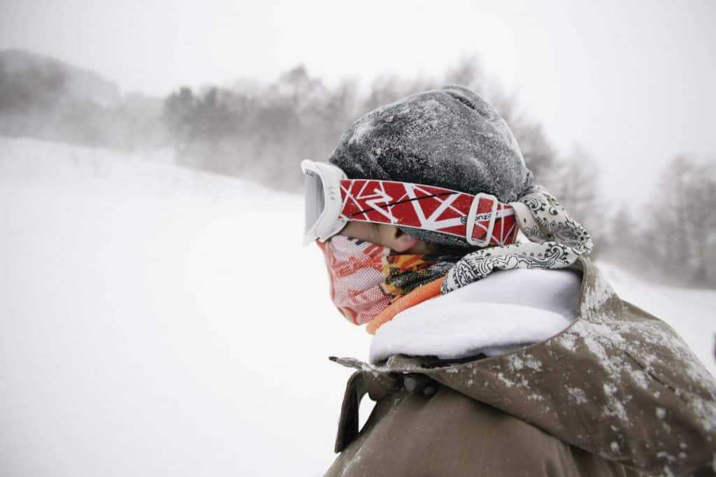 A landscape shot of a freestyle snowboarder. The conditions are rough. Strong winds are blowing snow around. He is wearing two Polar Buff®. One as scarf & face mask combination. The other one as hat / beanie. Source: buff.eu. Distributed for the promotion of the Polar Buff®