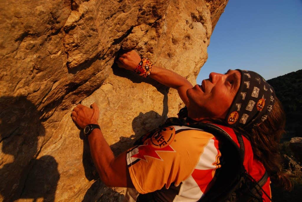 A member of the Buff® Adventure Racing Team climbing up a cliff. He is wearing a Original Buff® as sweatband. © Original Buff S.A. Released for the promotion of Buff® products