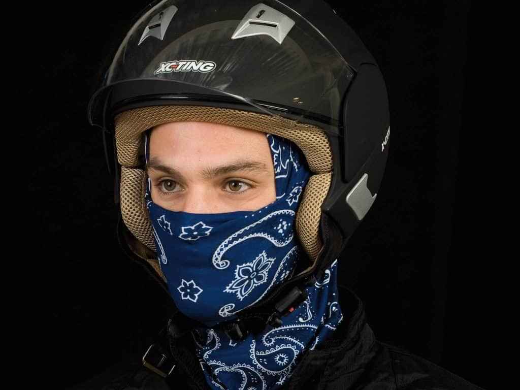 A portrait frontal, full face photo of a man wearing a Original Buff® as helmet liner under his open face motorcycle touring helmet. A studio photoshoot with Buff® ambassador Jordi Viladoms in front of a black background. Jordi is wearing the Original Buff® as helmet liner. The front is pulled up to his nose as face mask. Source: buff.eu Copyright: © Original Buff® S.A. Released for the promotion of the Original Buff® in motorcycling.