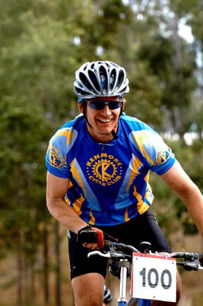 """The image shows John from Kenmore Cycles during the 2004 Kooralbyne 24 hour MTB XC race. He is wearing a Original Buff® as legionnaire cap under his helmet. This keeps the sweat out of his eyes and gives heat relief. I mention the High UV Buff® in the caption because today this would be your preferred product for this situation. The High UV Buff® excels in handling sweat & heat. The photo is a vertical shot showing John from the handlebars upwards. John is smiling and it looks as if he is having a great time. He is wearing mountain bike gloves, a short sleeved """"Kenmore Cycle Club"""" cycling jersey, blue tinted sunglasses and a helmet with big vents. The Buff® is clearly visible under the helmet. Photographer: Unknown Copyright: Unknown but we received the images as part of being sponsors with the right to use commercially"""