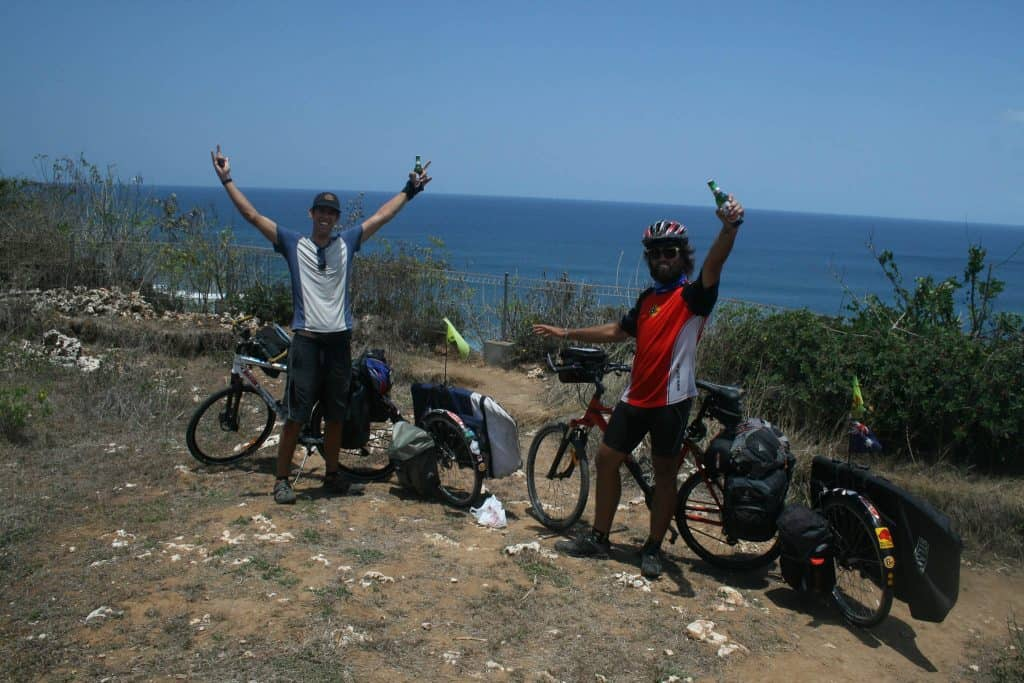 """The Horizontal photo shows Rian and Dylan standing with their bicycles on the cliff of Uluwatu, Bali, Indonesia. They have cycled Indonesia from North to South and are celebrating their successful journey. Dylan is holding both arms up as a victory sign. Rian has got one arm up. He is holding a beer. Rian is wearing the Australia Flag Original Buff® as neck cooler. It appears mid day with hardly any shadow and a clear blue sky. It must be hot. Source: Eatsleepsurf.com.au Copyright: Unknown. We received the images as """"Thank You"""" for providing the Buff®"""