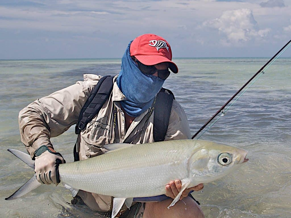A frontal landscape shot of a fly fisherman standing up to his hips in water. The man is holding a large milkfish in his hands. He is wearing a High UV Buff® as face mask. Addional cap, long sleeve shirt and cap indicate that he wants total UV protection. Source: buff.eu Copyright: ©2007 Pat Ford. Given to us for the promotion of the High UV Buff® in the fishing market