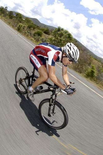 """A vertical photo of a male riding a XC mountain bike in the centre of a bitumen road. The rider is wearing a red & blue Simplon team jersey and cycle shorts. Under his white mtb helmet you can spot the Crocodile Trophy High UV Buff®. He is wearing it as a legionnaire cap covering his head and his back neck. The speed is fast paced and the surroundings looks like the can fields north of Port Douglas in North Queensland. Source: Crocodile Trohpy Photographer unknown Copyright: Unknown. We received this low-res images as """"Thank-You"""" for providing the High UV Buff®"""
