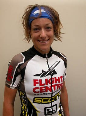 """The photo is vertical and shows female MTB rider Tory standing upright in front of a grey wall. She is wearing a Flightcentre Scott team cycle jersey and a Original Australia Flag Buff® as Alice Band. Her tired smile and her hair suggest that the photo is taken after a XC race. She smiles tired but happy. The Buff® as Alice Band keeps her hair together and tidy. Photographer: Unknown Copyright: Unknown. We received the image as a """"Thank-You"""" for providing the Flight Centre Scott MTB team with Australia Flag Buff®"""