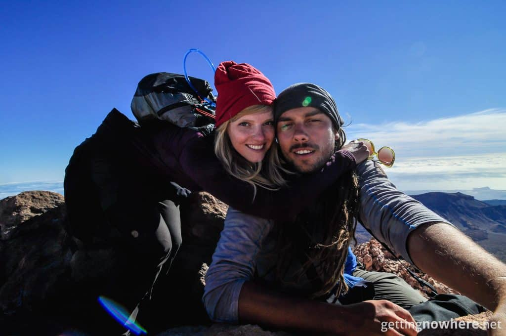 A landscape selfie showing a young man and woman smiling in the camera. They are sitting on top of a mountain peak. Their faces reveal exhaustion and happiness. They are both wearing Wool Buff® as beanies. Source: Gettingnowhere.net © Permission to use on our websites