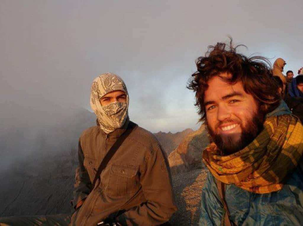 A side landscape selfie of two men smiling in the camera. They are high up in the mountains nearly in the clouds. The right person Rian Cope sports lots of facial hair and a big scarf. The left person is using a Original Buff® to entirely cover his head. Only the eyes are uncovered. Source: Rian Cope www.EatSleepSurf.com.au © Allowed to use on our website