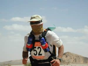 A participant of the Marathon Des Sables running through the desert. He is wearing a custom made High Uv Buff® as face mask. Copyright is unknown. Distributed by Original Buff® S.A. for the promotion of Buff® products