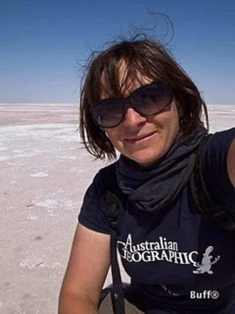 A portrait selfie of Danielle Murdoch somewhere in the middle of nowhere. She is wearing a short sleeve Australian Geographic T-shirt and a grey Wool Buff® as scarf. The hair looks a bit scruffy as if she just took her motorcycle helmet off. She appears to be in her comfort zone and looks happy. Source: Danielle Murdoch motomonkeyadventures.com © permission to use on our websites